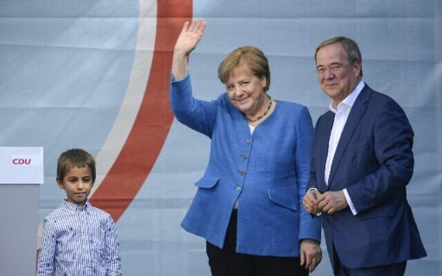 Christian Democratic Union CDU leader and chancellor candidate Armin Laschet (R) and German Chancellor Angela Merkel react on stage during their campaign rally in Aachen, western Germany, on September 25, 2021, one day ahead of the German federal elections. (Ina Fassbender / AFP)