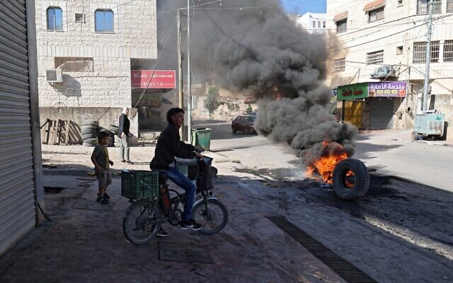 Burning tires block the entrance of the Palestinian village of Burqin, west of Jenin, in the West Bank, following exchanges of gunfire during an arrest raid by Israeli forces, on September 26, 2021. (Jaafar Ashtiyeh/AFP)