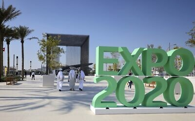 People walk past the official Expo 2020 sign at the Dubai Expo in the United Arab Emirates, January 16, 2021. (Photo by Karim SAHIB / AFP)