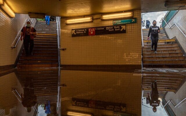 Commuters walk into a flooded 3rd Avenue / 149th st subway station and disrupted service due to extremely heavy rainfall from the remnants of Hurricane Ida on September 2, 2021, in New York City. (David Dee Delgado/Getty Images/AFP)
