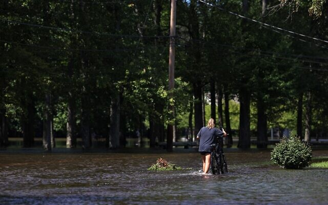 A girl walks a bike along a flooded West Williams Street, on September 2, 2021, in Lincoln Park, New Jersey. (Michael M. Santiago/Getty Images/AFP)
