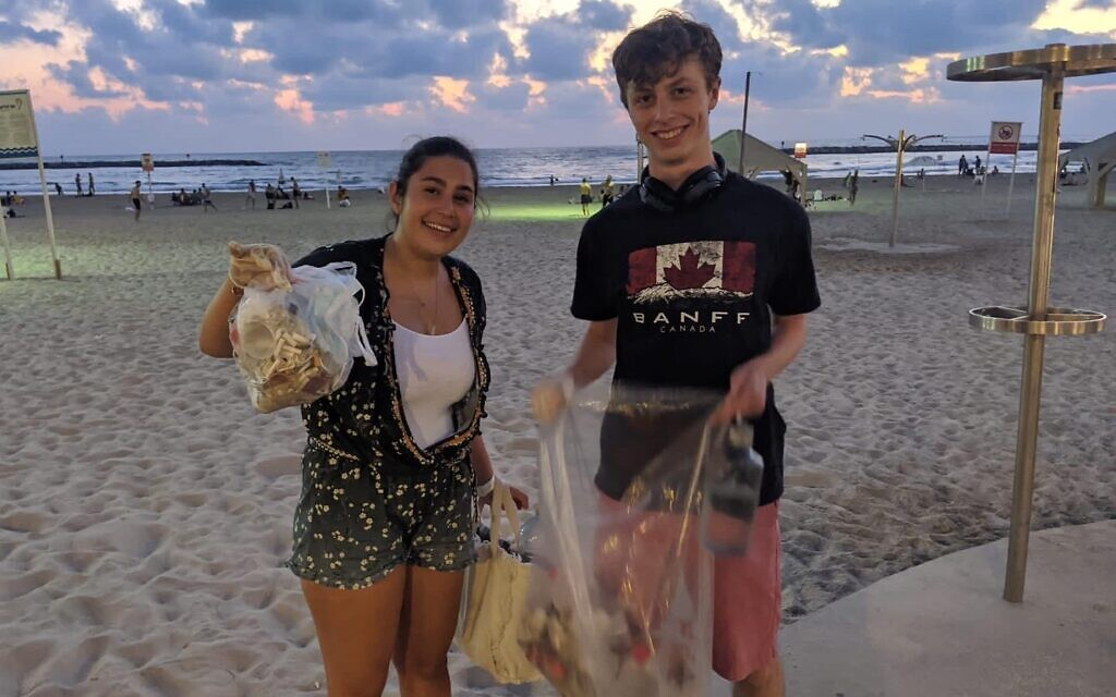 Sharona Shnayder picking trash from a beach in Tel Aviv along with a fellow volunteer in this undated photo. (Courtesy)