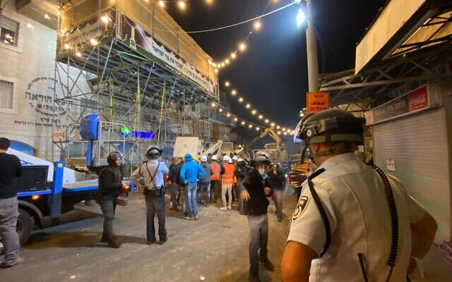 Police and Jerusalem city workers take apart a sukkah in Jerusalem's Mea Shearim neighborhood that was deemed a safety hazzard, September 19, 2021. (Israel Police)