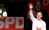 Olaf Scholz (M), Finance Minister and SPD candidate for Chancellor, waves to his audience and supporters during a campaign event at Schillerplatz in Nürtingen. (Bernd Weißbrod/picture alliance via Getty Images via JTA)