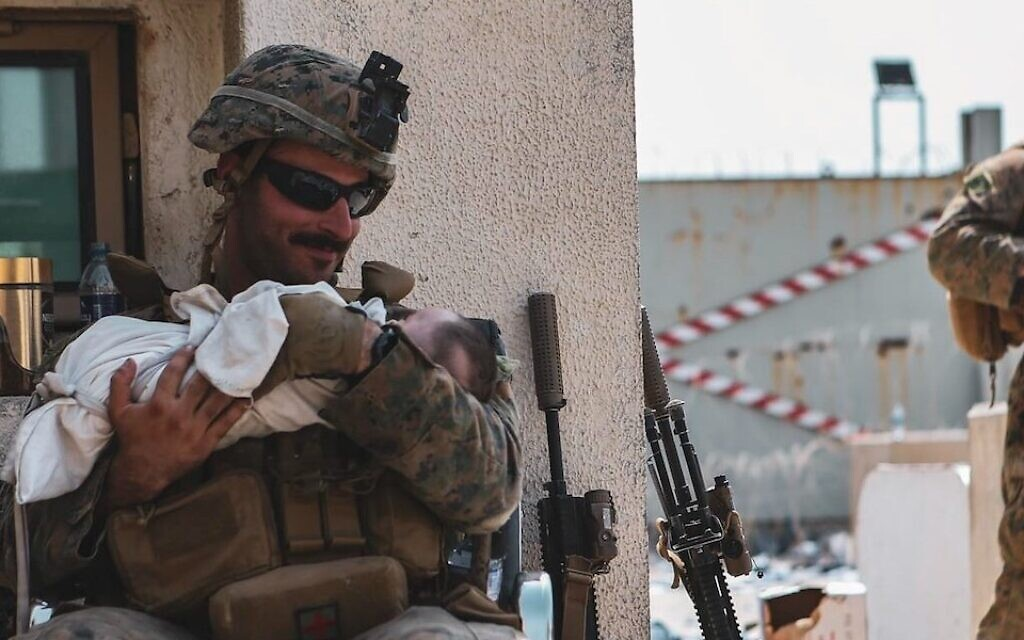 Matt Jaffe smiles at a baby at the Kabul airport in Afghanistan Friday, Aug. 20, 2021 in a photo that went viral. (U.S. Central Command Sgt. Isaiah Campbell/US Marine Corps)