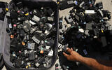 A man looks for a charger for his phone from a suitcase full of used chargers for sale in Los Angeles, on August 1, 2018. (AP Photo/Jae C. Hong)