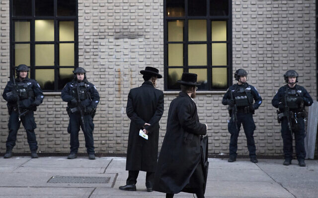 In this illustrative photo from December 11, 2019, Orthodox Jewish men pass by New York City police guarding a Brooklyn synagogue prior to a funeral for Mosche Deutsch, a rabbinical student from Brooklyn who was killed in a shooting at a Jersey City, New Jersey, market. (AP Photo/Mark Lennihan, File)