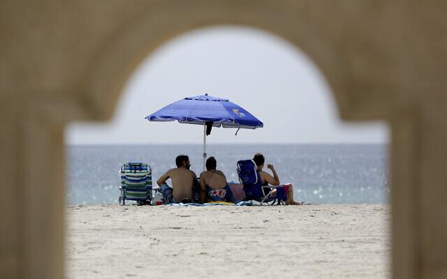 People sit on Hollywood Beach on July 2, 2020, in Hollywood, Fla. (AP Photo/Lynne Sladky)