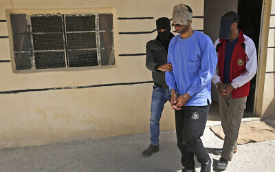"""In this file photo dated Friday, March 30, 2018, a Kurdish security officer escorts Alexanda Kotey, in blue, and El Shafee Elsheikh, who were allegedly among four British jihadis who made up a brutal Islamic State cell dubbed """"The Beatles,"""" at a security center in Kobani, Syria.  (AP/Hussein Malla)"""