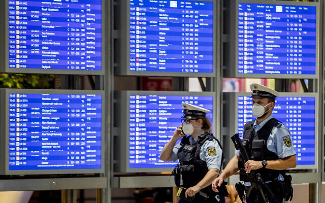 Illustrative: German police officers wearing face mask walk past a flight board in a terminal at the airport in Frankfurt, Germany, on May 11, 2021. (AP/Michael Probst)