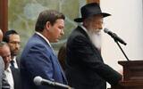 Florida Gov. Ron DeSantis, left, and Rabbi Sholom Lipskar participate in a moment of silence, June 14, 2021, at The Shul of Bal Harbour, Florida. (AP Photo/Wilfredo Lee)
