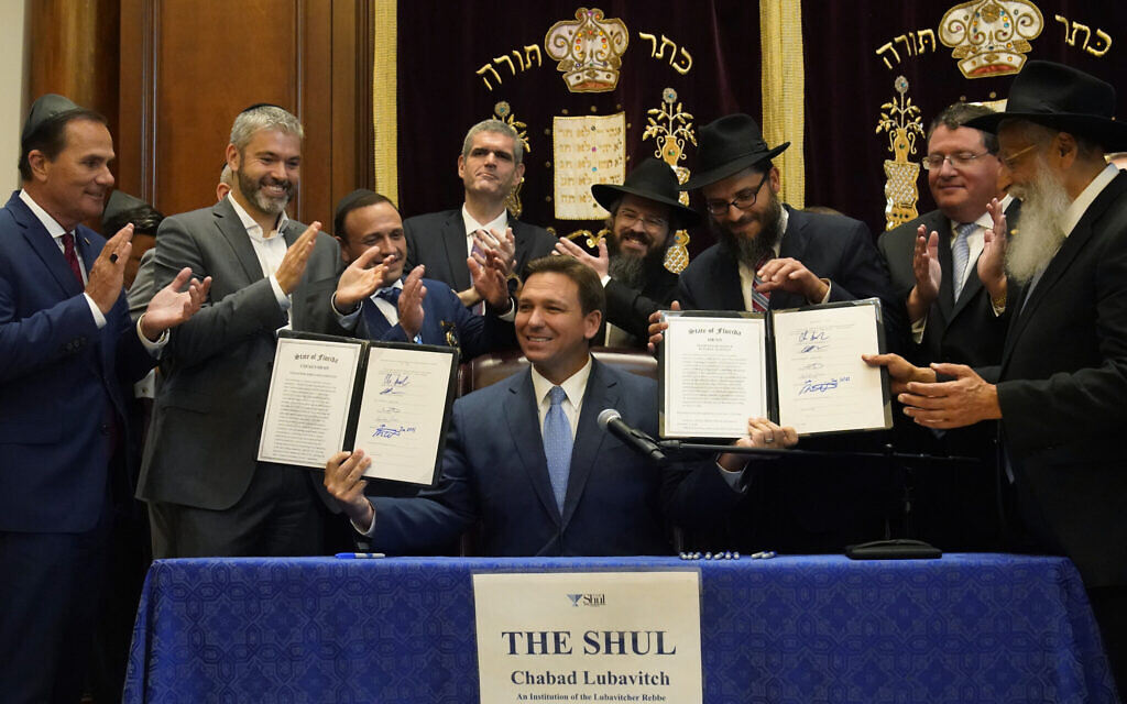 Surrounded by state legislators and Jewish leaders, Florida Gov. Ron DeSantis, center, holds up two bills that he signed on June 14, 2021, at The Shul of Bal Harbour, a Jewish community center in Surfside, Florida. (AP Photo/Wilfredo Lee)