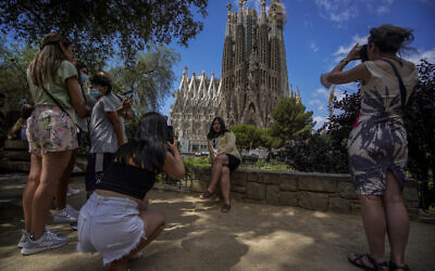 Tourists take pictures in front of Sagrada Familia Basilica designed by architect Antoni Gaudi in Barcelona, Spain, Friday, July 9, 2021. (AP Photo/Joan Mateu)