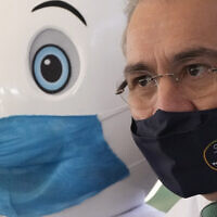 Brazilian Health Minister Marcelo Queiroga stands next to the mascot promoting the vaccination campaign as he gives shots of the AstraZeneca COVID-19 vaccine at a vaccination center in Brasilia, Brazil, Wednesday, July 14, 2021. (AP Photo/Eraldo Peres)