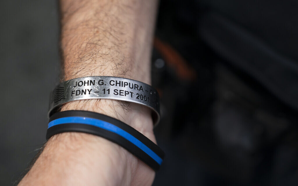 NYPD officer Michael Dougherty, a 25-year veteran, displays a bracelet bearing the name of John G. Chipura, an FDNY firefighter and former Marine who died responding to the attacks, as he stands beside the south reflecting pool of the 9/11 Memorial & Museum where names of his deceased colleagues and friends are displayed, Aug. 16, 2021, in New York (AP Photo/John Minchillo)