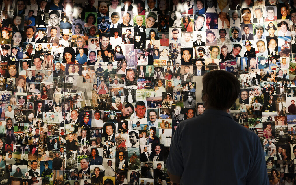 Désirée Bouchat, a survivor of the 9/11 attacks on the World Trade Center, looks at photos of those who perished, in a display at the 9/11 Tribute Museum, on Friday, August 6, 2021, in New York. (AP Photo/Mark Lennihan)