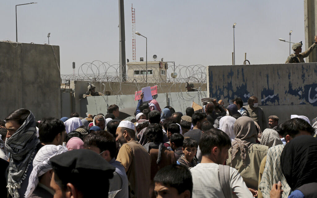 US soldiers stand inside the airport wall as hundreds of people gather near an evacuation control checkpoint on the perimeter of the Hamid Karzai International Airport, in Kabul, Afghanistan, August 26, 2021. (AP Photo/Wali Sabawoon)
