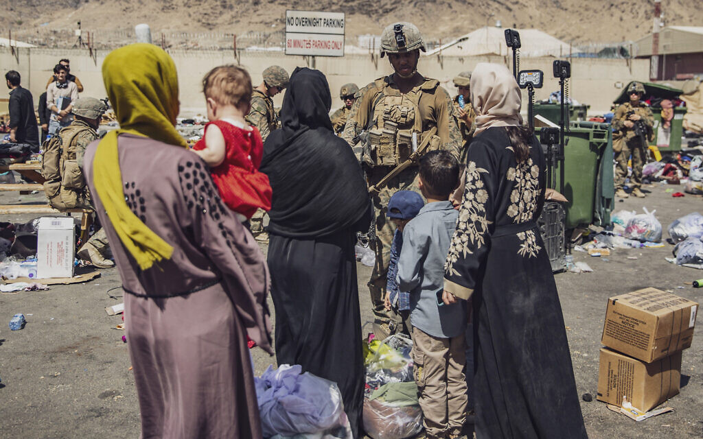In this image provided by the US Marine Corps, Marines with the 24th Marine Expeditionary Unit process evacuees as they go through the evacuation control center at Hamid Karzai International Airport in Kabul, Afghanistan, August 28, 2021. (Staff Sgt. Victor Mancilla/U.S. Marine Corps via AP)