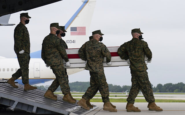 President Joe Biden watches as a carry team moves a transfer case containing the remains of Marine Corps Lance Cpl. Jared M. Schmitz, 20, of St. Charles, Mo., during a casualty return Sunday, Aug. 29, 2021, at Dover Air Force Base, Del. According to the Department of Defense, Schmitz a died in an attack at Afghanistan's Kabul airport, along with 12 other U.S. service members. (AP Photo/Carolyn Kaster)
