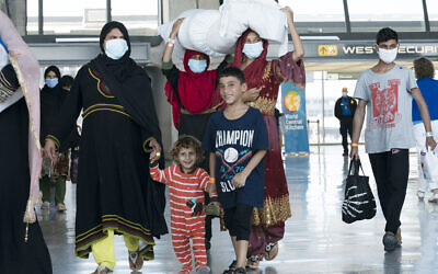 Illustrative: Families evacuated from Kabul, Afghanistan, walk through the terminal before boarding a bus after they arrived at Washington Dulles International Airport, in Chantilly, Virginia, August 30, 2021. (AP Photo/Jose Luis Magana)