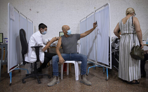 An Israeli man takes a selfie while receiving the third Pfizer-BioNTech COVID-19 vaccine from medical staff at a coronavirus vaccination center in Ramat Gan, Israel, Aug. 30, 2021 (AP Photo/Oded Balilty)