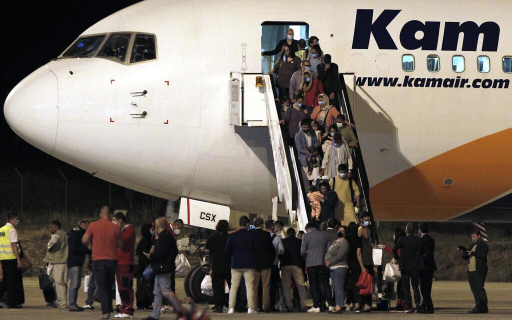Afghan evacuees disembark from a plane after landing at Skopje International Airport, North Macedonia, August 30, 2021. (AP Photo/Boris Grdanoski)
