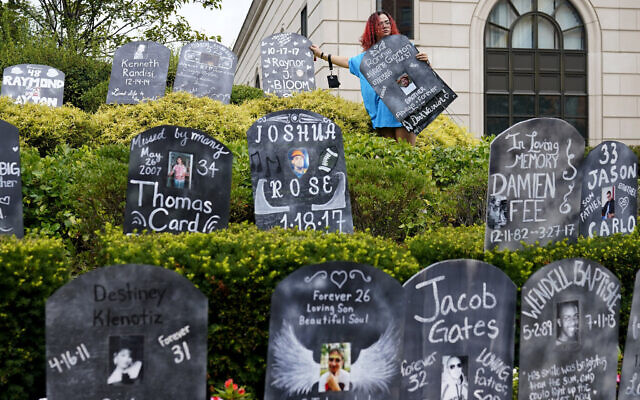 In this Aug. 9, 2021, file photo, Jayde Newton helps to set up cardboard gravestones with the names of victims of opioid abuse outside the courthouse where the Purdue Pharma bankruptcy is taking place in White Plains, N.Y. A federal bankruptcy judge on Wednesday, Sept. 1, gave conditional approval to a sweeping, potentially $10 billion plan submitted by OxyContin maker Purdue Pharma to settle a mountain of lawsuits over its role in the opioid crisis that has killed a half-million Americans over the past two decades. (AP Photo/Seth Wenig, File)