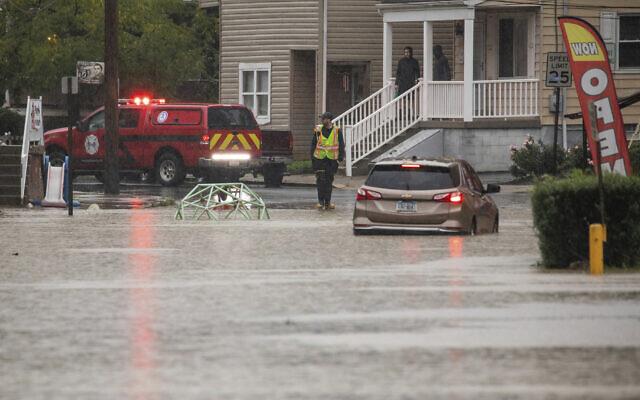 A car is stranded on a flooded street September 1, 2021, in Bridgeville, Pennsylvania. (Andrew Rush/Pittsburgh Post-Gazette via AP)
