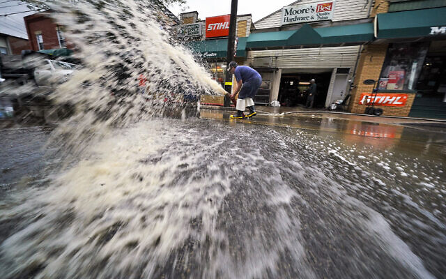 Water is pumped from the basement of a business on Noblestown road in Oakdale, Pennsylvania, during clean up from flooding after downpours and high winds from the remnants of Hurricane Ida hit the area September 1, 2021. (AP Photo/Gene J. Puskar)