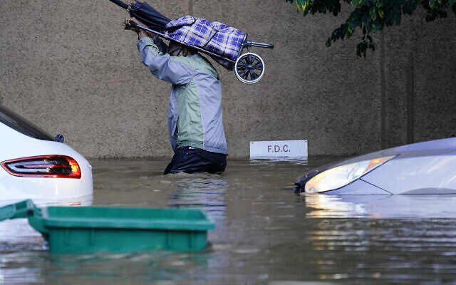 A person walks in floodwaters in Philadelphia, on Thursday, September 2, 2021, in the aftermath of downpours and high winds from the remnants of Hurricane Ida that hit the area. (AP Photo/Matt Rourke)