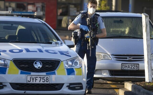 Armed police stand outside a supermarket in Auckland, New Zealand, Saturday, Sept. 4, 2021. New Zealand authorities say they shot and killed a violent extremist, Friday Sept. 3, after he entered a supermarket and stabbed and injured six shoppers. (AP Photo/Brett Phibbs)