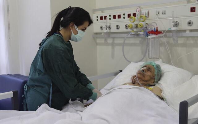 A nurse monitors Ayse Karatay at the City Hospital in Eskisehir, western Turkey, on September 4, 2021. (IHA via AP)