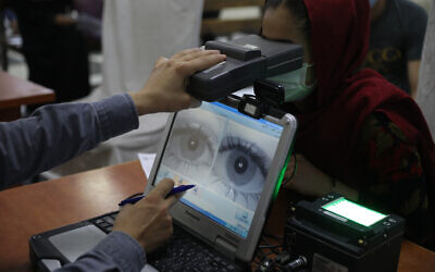 An employee scans the eyes of a woman for biometric data needed to apply for a passport, at the passport office in Kabul, Afghanistan, June 30, 2021. (AP Photo/Rahmat Gul, File)