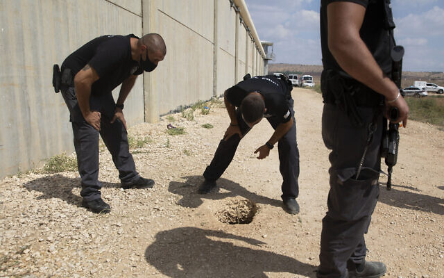 Police officers and prison guards inspect the scene of a prison escape outside the Gilboa prison in northern Israel, Monday, Sept. 6, 2021. (AP/Sebastian Scheiner)