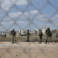 Israeli soldiers stand guard near a damaged section of the border fence, near the West Bank village of Jalameh, September 6, 2021. (AP/Nasser Nasser)