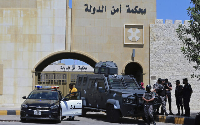 Officers stand guard outside Jordan's State Security Court in Amman, where two former officials, accused of helping Jordanian Prince Hamzah try to overthrow his half-brother King Abdullah II, await a verdict in their trial, on July 12, 2021. (AP Photo/Raad Adayleh, File)