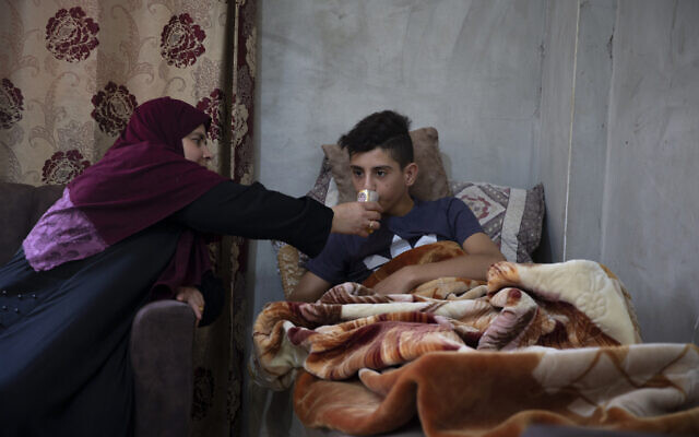 Tareq Zubeidi, 15, rests at his house, in the West Bank village of Silat ad-Dhahr, Tuesday, August 31, 2021. (AP/Majdi Mohammed)