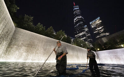 James Maroon, left, cleans the bottom of the south pool of the 9/11 Memorial with a vacuum, Aug. 4, 2021, in New York (AP Photo/Mark Lennihan)