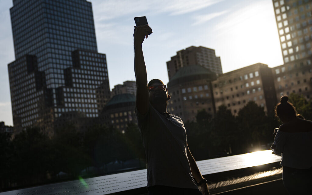 A visitor takes a selfie beside the north pool at the National September 11 Memorial & Museum, Wednesday, Sept. 8, 2021, in New York. (AP Photo/John Minchillo)