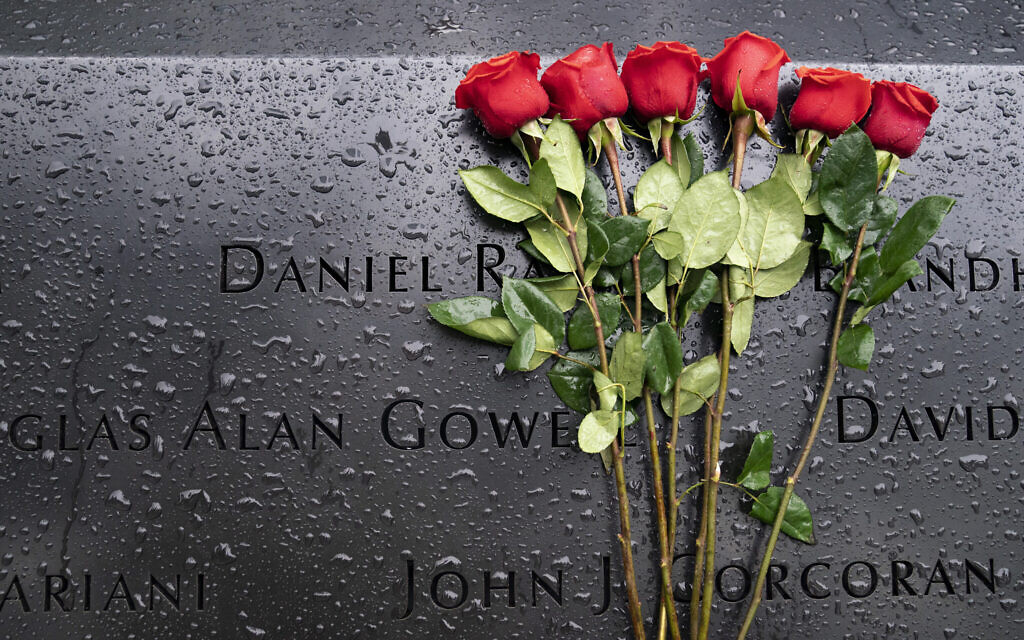 Red roses rest against the names of the fallen on the south pool at the National September 11 Memorial & Museum, Sept. 9, 2021, in New York. (AP Photo/John Minchillo)