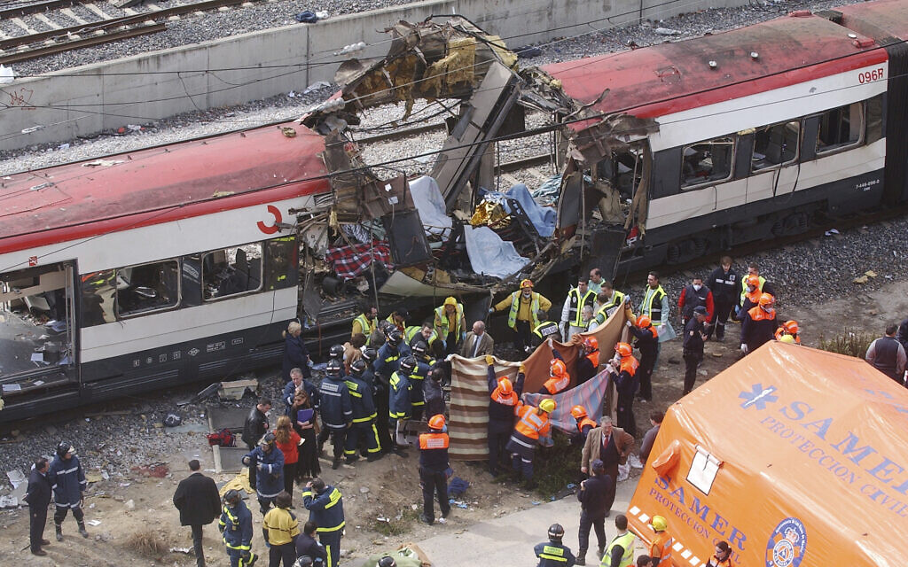 In this March 11, 2004 file photo rescue workers cover up bodies alongside a bomb-damaged passenger train, following a number of explosions in Madrid, Spain, March 11, 2004. (AP Photo/Paul White, File)
