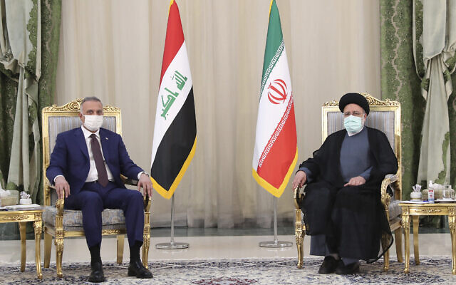 In this photo released by the official website of the office of the Iranian Presidency, President Ebrahim Raisi, right, and Iraqi Prime Minister Mustafa al-Kadhimi sit during their meeting in Tehran, Iran, Sunday, Sept. 12, 2021. (Iranian Presidency Office via AP)