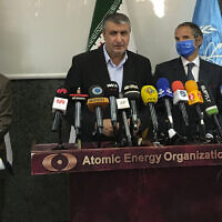 The head of the Atomic Energy Organization of Iran, Mohammad Eslami (center) speaks during a joint press briefing with Director General of International Atomic Energy Agency Rafael Mariano Grossi (second right) in Tehran, Iran, on Sunday, September 12, 2021. (Atomic Energy Organization of Iran via AP)