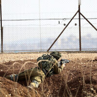 An Israeli soldier takes position along the border between the northern West Bank near Jenin and Israel as they search for two Palestinians who broke out of a maximum-security prison last week, on a road leading to the West Bank town of Jenin, near Gan Ner Israel, September 12, 2021. (Ariel Schalit/AP)