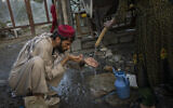 A displaced Afghan man drinks from a water tank at an internally displaced persons camp in Kabul, Afghanistan, September 13, 2021. (Bernat Armangue/AP)