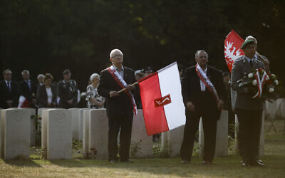 People with Polish flags attend a wreath laying ceremony to commemorate the Nazi German invasion of Poland and the beginning of World War II at the British War Cemetery in Berlin, Germany, September 1, 2019. (AP Photo/Markus Schreiber, File)