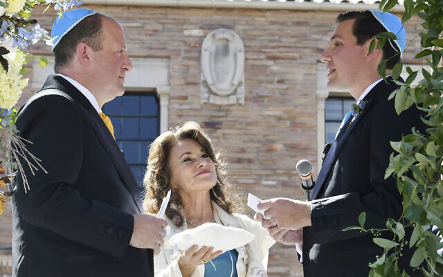 In this photo provided by Jocelyn Augustino, Rabbi Tirzah Firestone, center, officiates a traditional Jewish wedding ceremony attended by family and friends for Colorado Gov. Jared Polis, left, and his partner, Marlon Reis, in Boulder, Colorado, on September 15, 2021. (Jocelyn Augustino via AP)