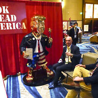 In this Feb. 26, 2021, file photo, Look Ahead America sponsor Matt Braynard, center, talks to conference attendees at his booth in the merchandise show with a statue of former president Donald Trump at the Conservative Political Action Conference (CPAC) in Orlando, Fla. (AP Photo/John Raoux, File)