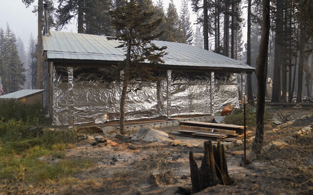 In this September 2, 2021 file photo, cabin partially covered in fire-resistant material stands next to properties destroyed in the Caldor Fire in Twin Bridges, CA. (AP/Jae C. Hong,File)