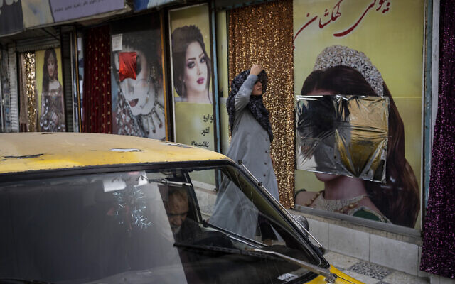 A woman walks past beauty salons with window decorations which have been defaced in Kabul, Afghanistan, Sept. 12, 2021 (AP Photo/Bernat Armangue)